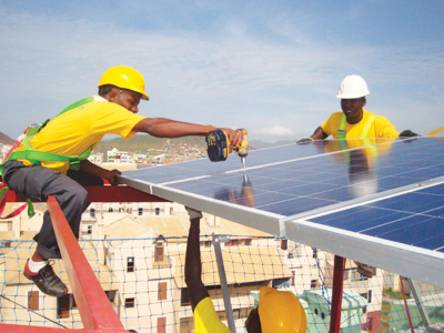 workers on a rooftop in West Africa, installing solar panels